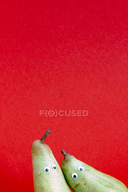 Par de peras delante de fondo rojo - foto de stock