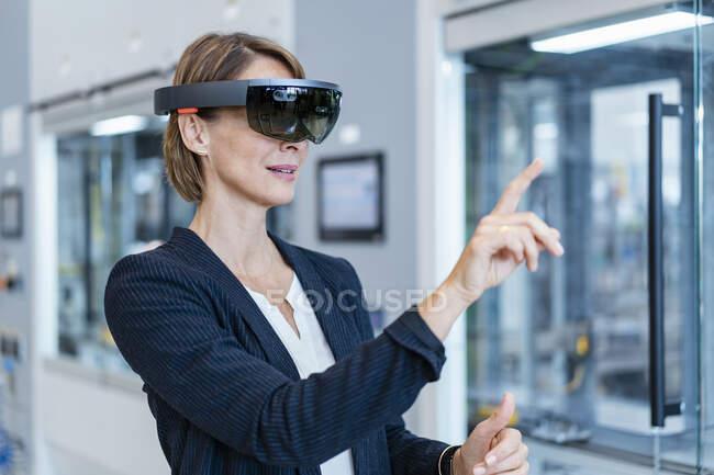 Empresaria con gafas AR en una fábrica moderna - foto de stock