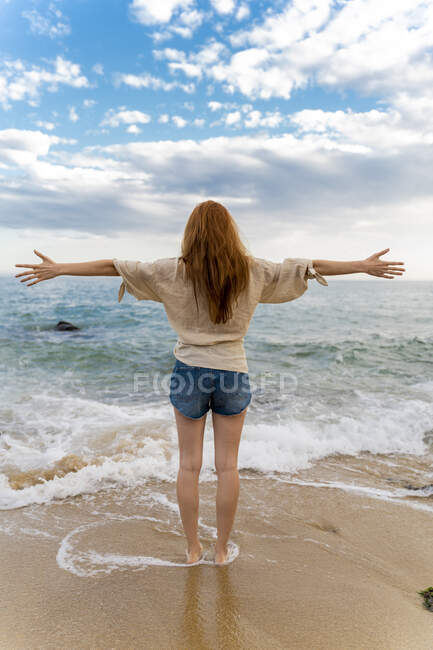 Back view of redheaded young woman standing at seafront with arms outstretched — Stock Photo