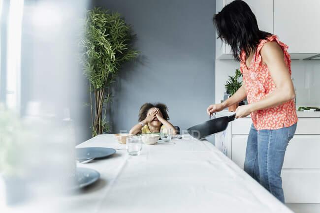 Мама готує їжу для дочки за обіднім столом. — стокове фото