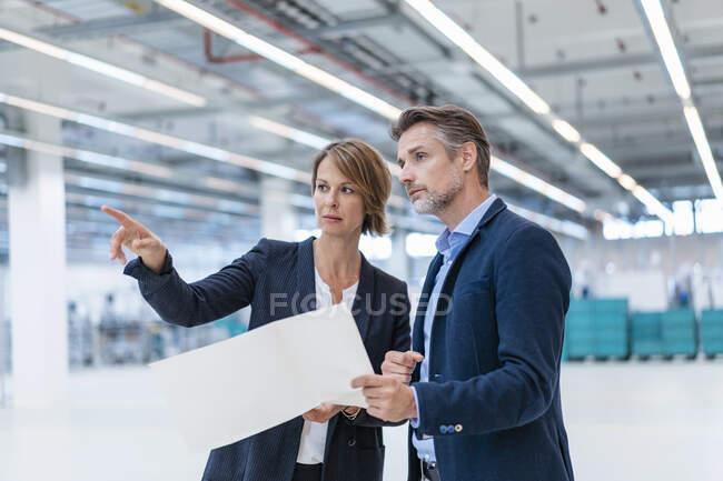 Empresario y empresaria discutiendo plan en una fábrica - foto de stock