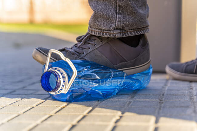 Close-up of man's feet sqashing plastic bottle for recycling — Stock Photo