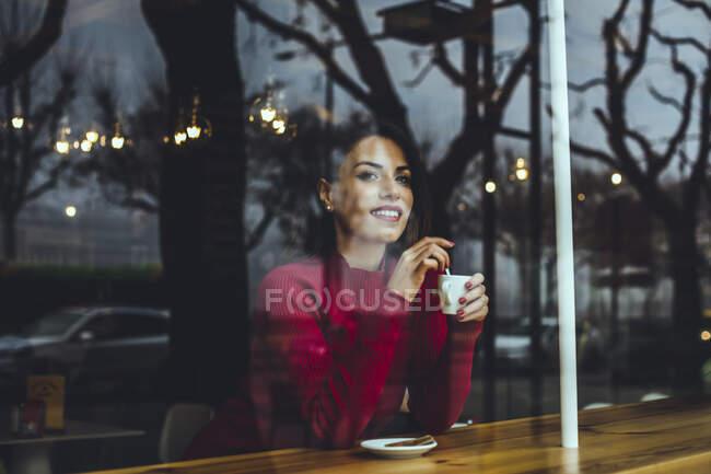 Mujer joven sonriente con taza de café detrás del cristal de una ventana en un café - foto de stock