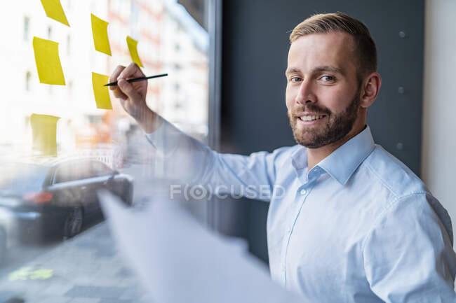 Portrait of smiling businessman writing on adhesive notes at glass pane — Stock Photo
