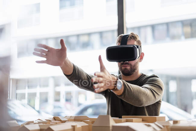Man with architectural model in office wearing VR glasses — Stock Photo