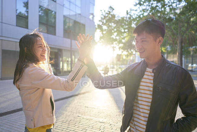 Smiling couple high fiving at sunset — Stock Photo