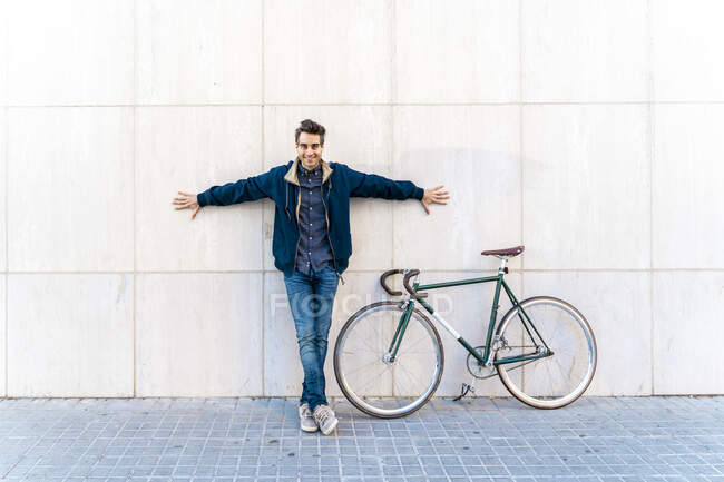 Portrait of casual man with bicycle standing at a wall — Stock Photo