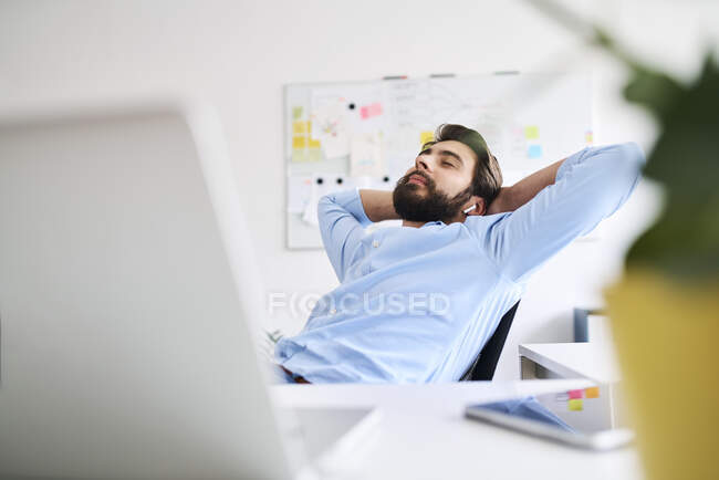 Businessman relaxing at a desk — Stock Photo