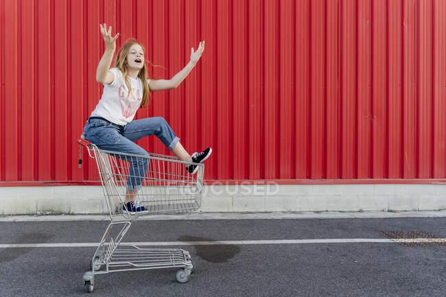 Chica en un carrito de compras en frente de la pared roja - foto de stock