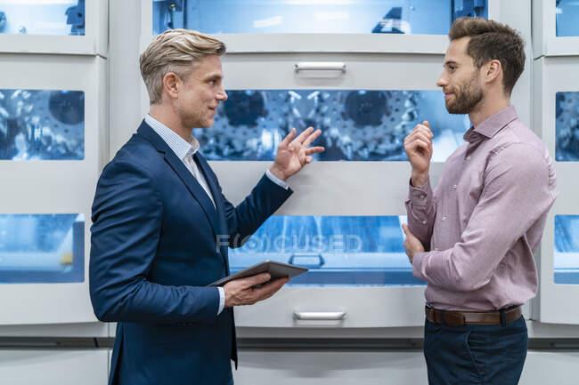Dos hombres de negocios con tableta hablando en la máquina en una fábrica moderna - foto de stock