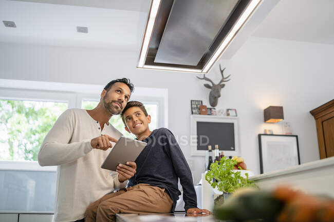 Батько і син користуються планшетом на кухні. — стокове фото