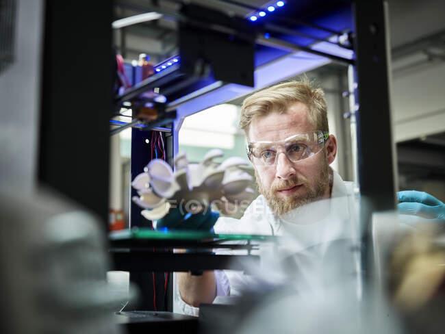 Техник, распечатывающий колесо турбины на 3D принтере — стоковое фото