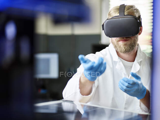 Technician with VR glasses and solar panel in lab — Stock Photo
