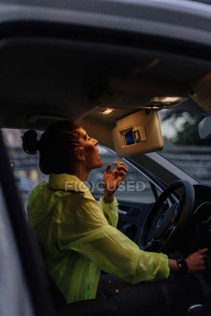 Sporty woman sitting in car, checking make up after workout — Stock Photo