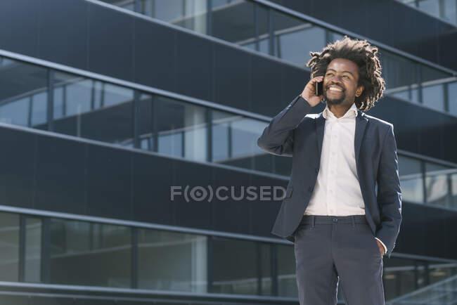 Hombre de negocios sonriente hablando por teléfono celular fuera de la oficina - foto de stock