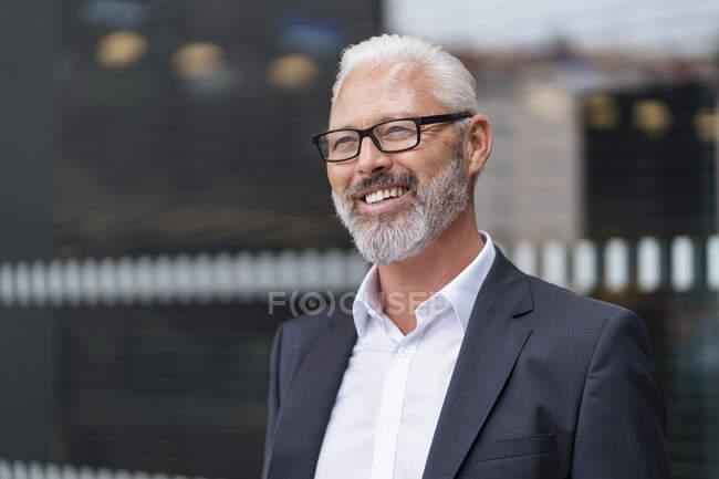 Retrato de hombre de negocios maduro sonriente con gafas - foto de stock
