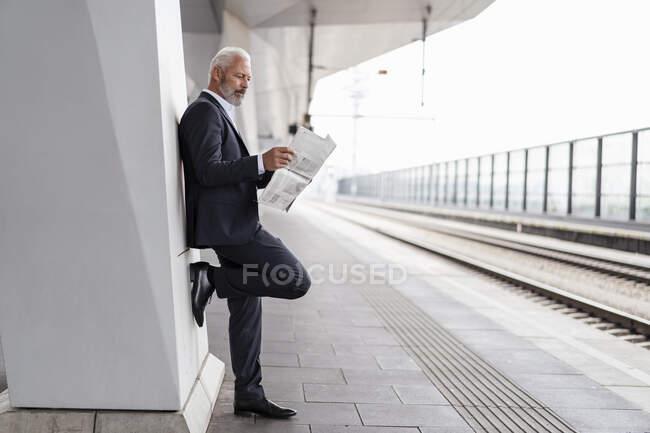 Зрелый бизнесмен читает газету на вокзале — стоковое фото