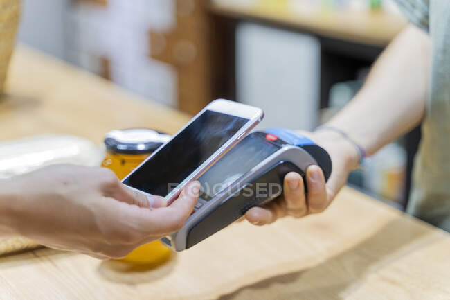 Cliente pagando sin efectivo con smartphone en una tienda - foto de stock