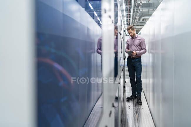 Empresario usando tableta en una máquina en una fábrica - foto de stock
