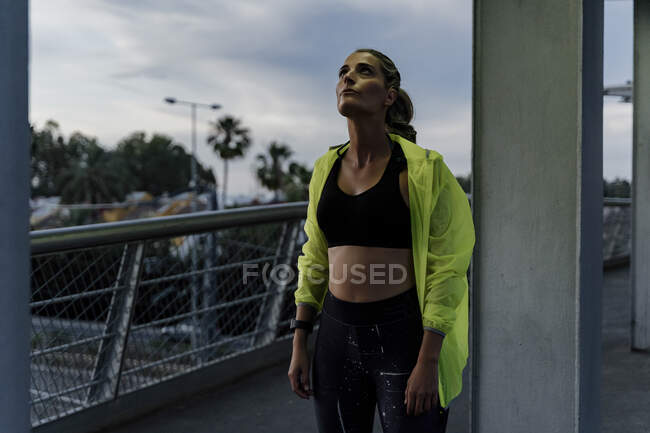 Sporty woman standing on a bridge, looking up — Stock Photo