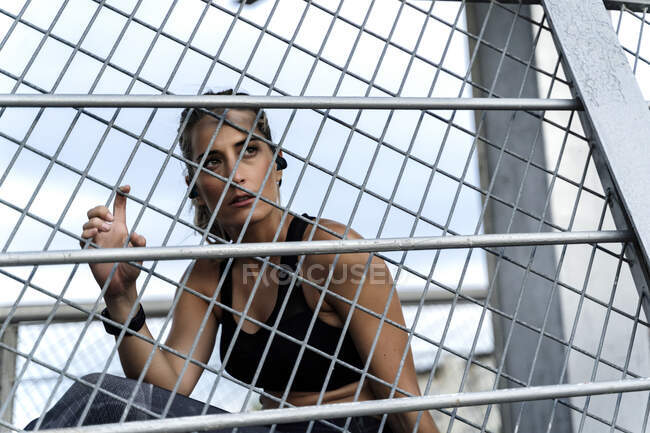 Sporty woman sitting on bridge, looking through grid — Stock Photo