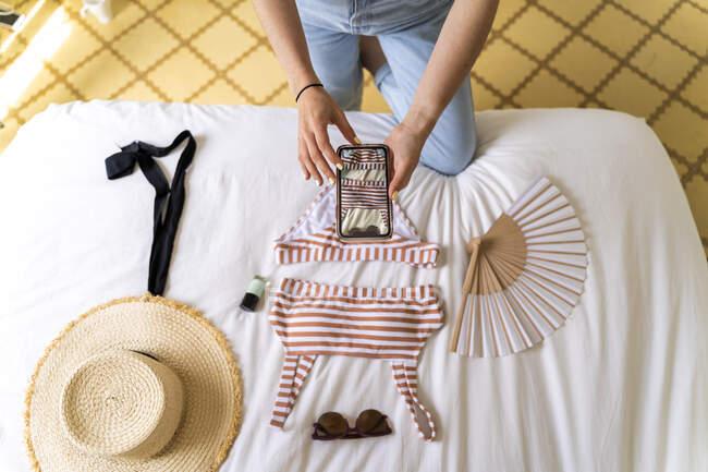 Mujer tomando foto de teléfono inteligente de bikini en la cama - foto de stock