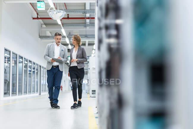 Geschäftsfrau und Geschäftsfrau mit Tablet laufen und sprechen in einer modernen Fabrik — Stockfoto