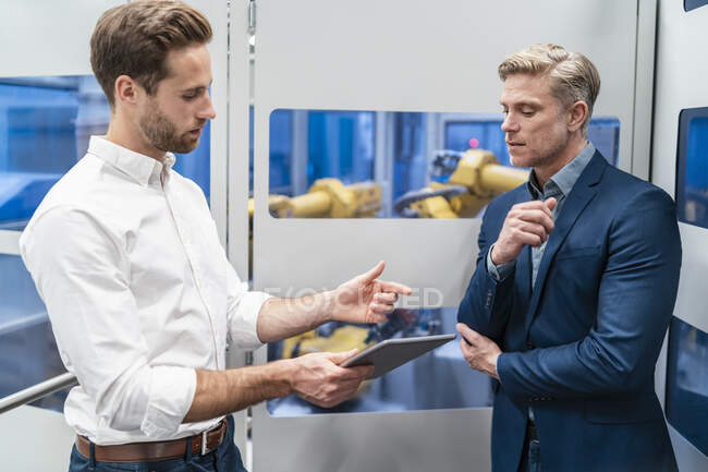Two businessmen talking at robot in a modern factory — Stock Photo