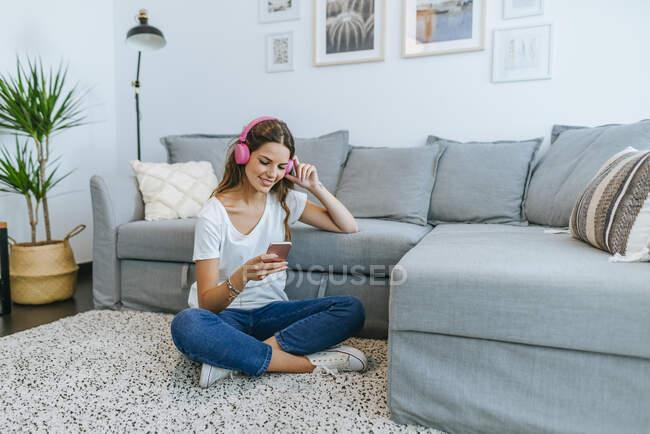 Giovane donna sorridente seduta sul pavimento in salotto ad ascoltare musica con il cellulare — Foto stock