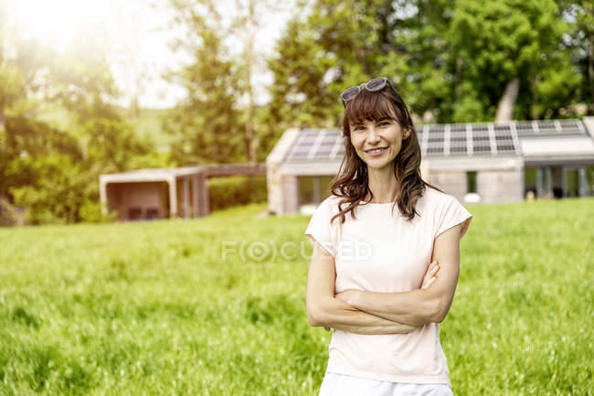 Portrait of smiling woman standing on meadow in front of a house — Stock Photo