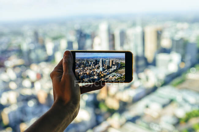 Close-up of man taking picture of the cityscape of Melbourne, Victoria, Australia - foto de stock