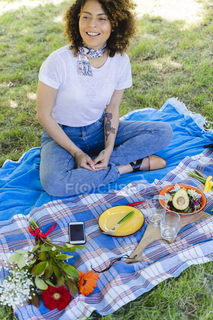 Relaxed smiling woman having a picnic in park — Stock Photo