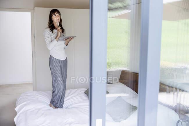 Donna in piedi sul letto a casa con tablet — Foto stock