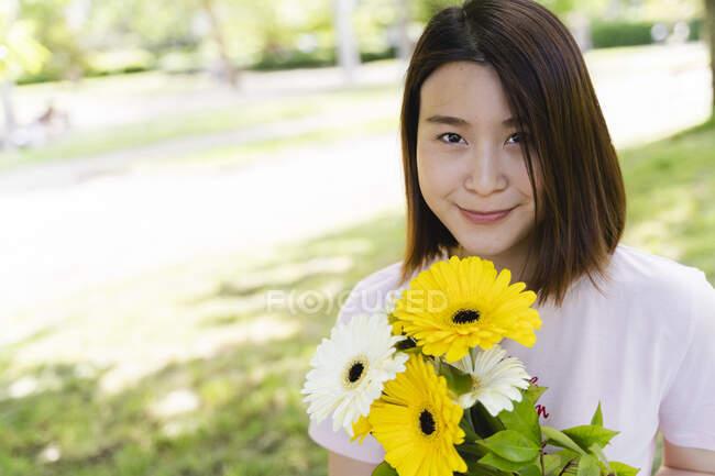 Ritratto di giovane donna sorridente con fiori nel parco — Foto stock