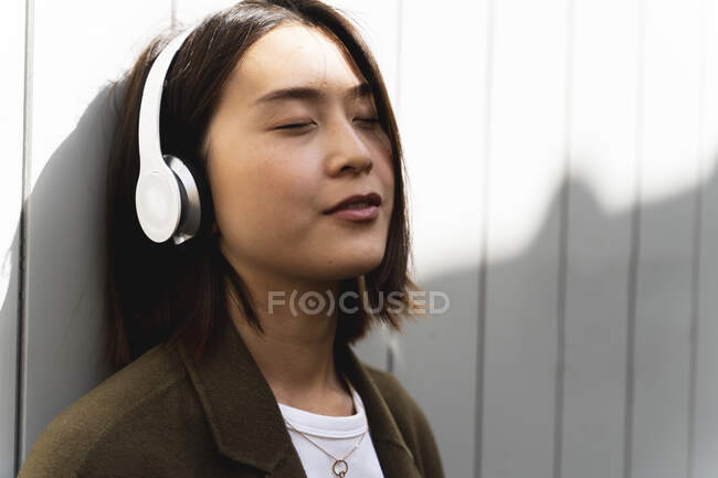Relaxed young woman with closed eyes listening to music with headphones — Stock Photo