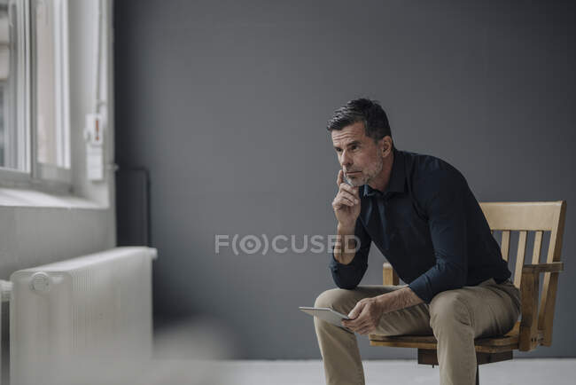 Зрілий бізнесмен сидить на стільці з планшетом. — стокове фото