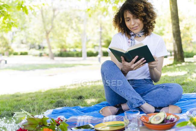Расслабленная женщина с книгой для пикника в парке — стоковое фото
