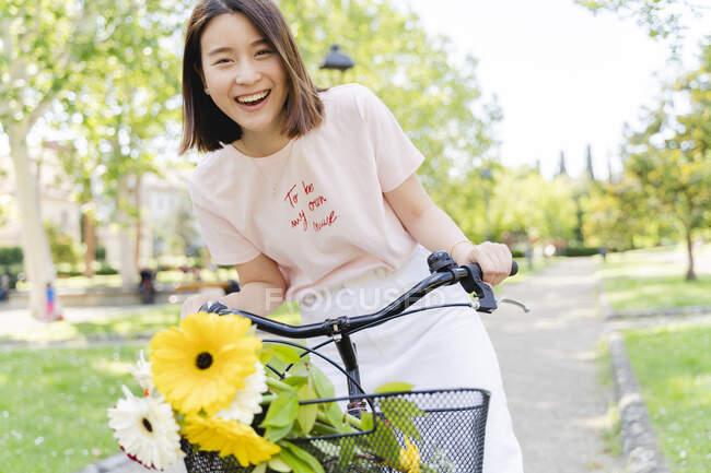 Портрет щасливої молодої жінки з квітами й велосипедами в парку. — стокове фото