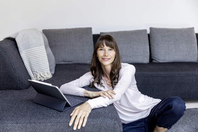 Ritratto di donna sorridente che utilizza tablet in soggiorno a casa — Foto stock