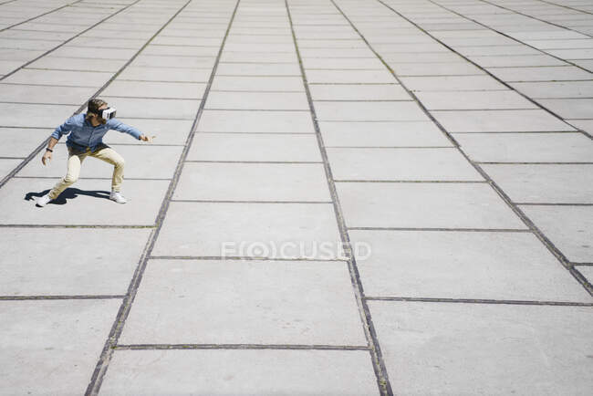 Young man with VR glasses standing on a square — Stock Photo