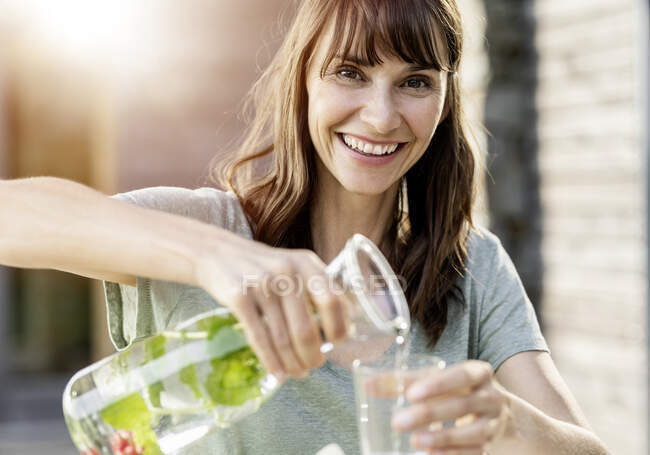 Portrait of happy woman pouring infused water into glass — Stock Photo
