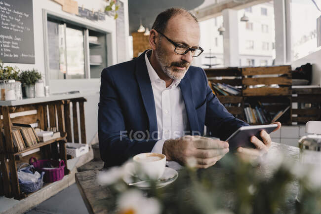 Mature businessman using tablet in a cafe — Stock Photo