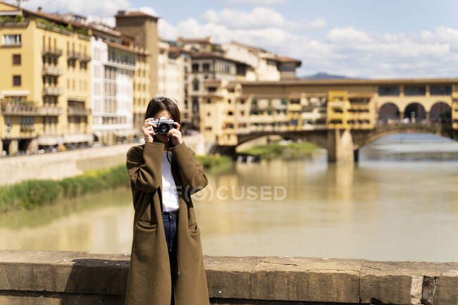 Italy, Florence, young tourist woman taking pictures at Ponte Vecchio — стоковое фото