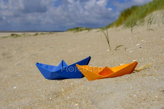 Barca di carta blu e arancione nella sabbia in spiaggia — Foto stock
