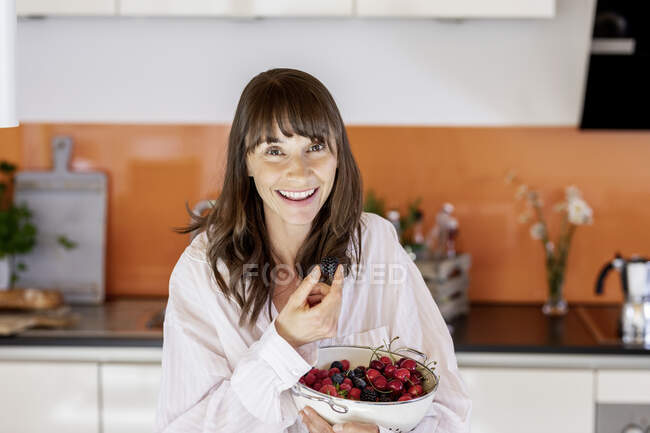 Portrait of happy woman wearing pyjama eating fruit in kitchen at home — Stock Photo