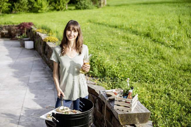 Portrait de femme souriante préparant la nourriture sur barbecue grill — Photo de stock