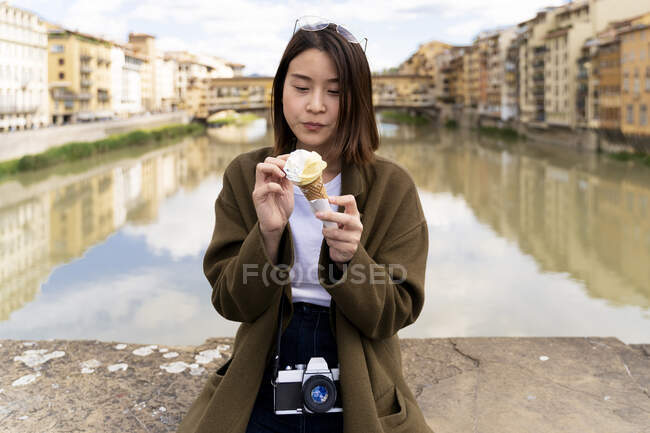 Italy, Florence, young tourist woman eating an ice cream cone at at Ponte Vecchio — Stock Photo