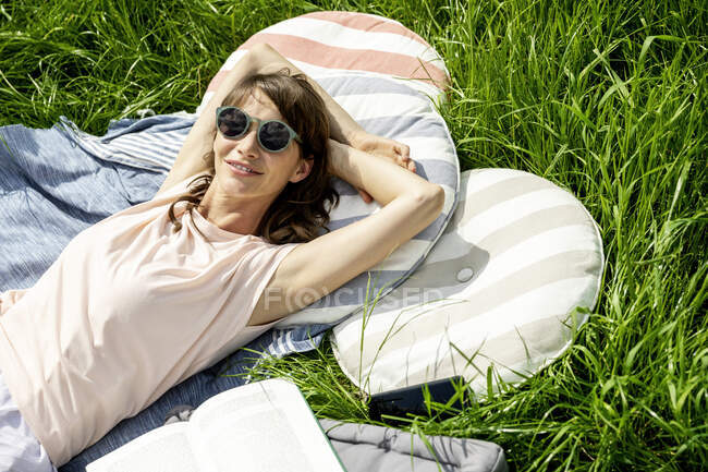 Portrait of smiling relaxed woman lying on a meadow — Stock Photo
