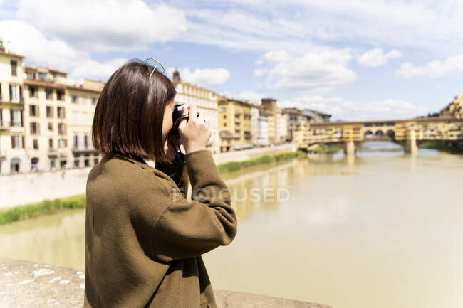 Italy, Florence, young tourist woman taking pictures at Ponte Vecchio — Photo de stock