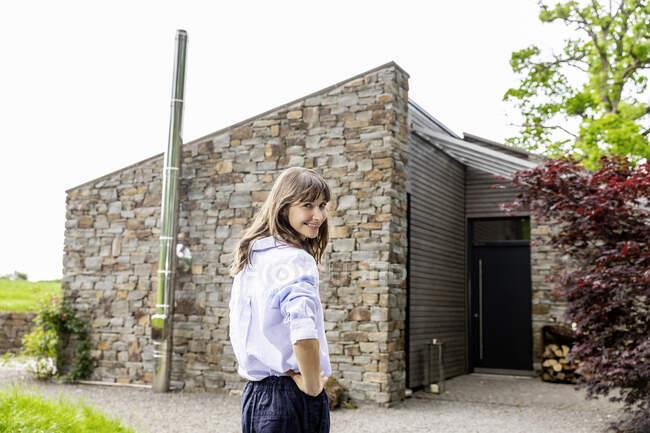 Sorrindo mulher de pé na frente de uma casa — Fotografia de Stock